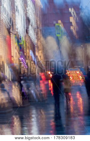 Abstract background of blurred people figures under umbrellas, city street in rainy evening. Light illumination from lanterns and shop windows. Intentional motion blur. Concept of seasons, weather, modern city.