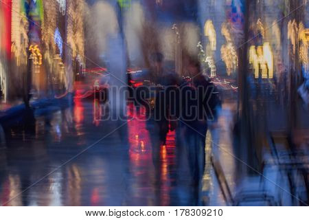 Abstract background in naturale blue tones. People walking down the city street in rainy evening. Intentional motion blur. Concept of seasons, weather, modern city, Impressionism style