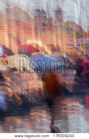 Abstract background of girl under umbrella in the city street in rain. Light illumination from lanterns and shop windows. Impressionism style. Intentional motion blur. Concept of seasons, weather, modern city.