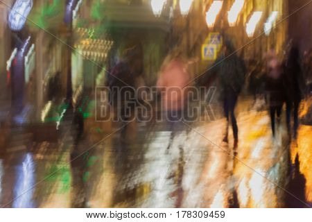 Abstract background of blurred young people walking down the street in rainy evening, Impressionism style, colorful lighting. Intentional motion blur. Concept of seasons, weather, modern city.