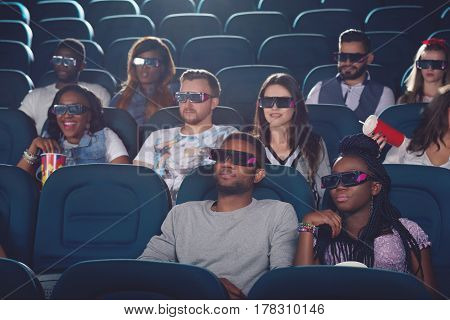Africans and caucasians watching movie in 3d glasses in modern cinema hall. Group of young people eating popcorn and drinking cola, spending free time in cinema.