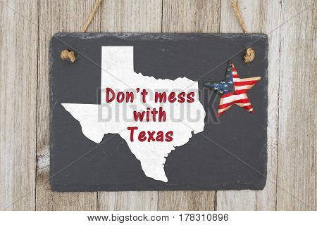 A rustic patriotic Texas message A retro chalkboard with a vintage USA star hanging and the state map of Texas on weathered wood background with text Don't mess with Texas