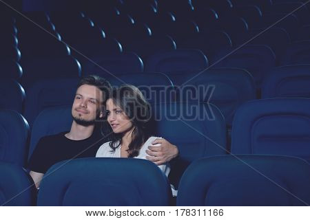 Handsome boyfriend with beard and pretty brunette girlfriend watching movie in cinema and sitting alone in hall. Couple embracing, girl leaning on boyfriend and touching by face.