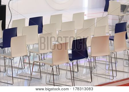 Conference chairs aligned in a row on a podium