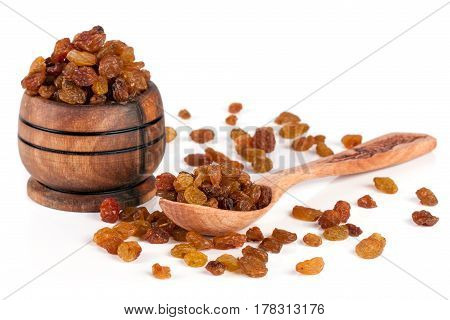 raisins in a wooden bowl with spoon isolated on white background.