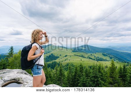 A young girl with a backpack standing on top of the mountain enjoying the view