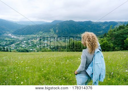 A young woman stands on top of a mountain in cloudy weather enjoying the view