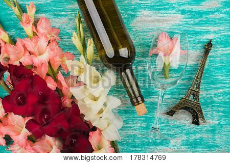 Light Pink And Red Gladiolus, Wineglass And Bottle Of Wine On The Azure Background