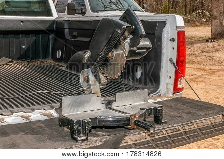 Miter saw on the tailgate of a pickup.