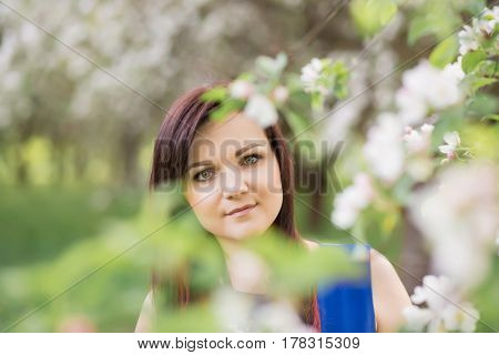 beautiful young brunette woman standing near the blossoming apple tree on a warm spring day.