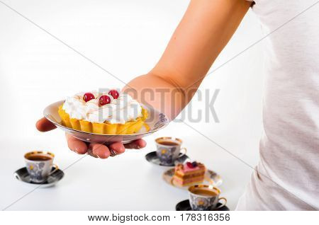 Woman's hand holding small cake on beautiful set plate