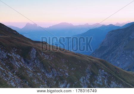 mountain ridge silhouettes in dusk before sunrise