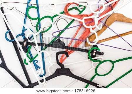 Many hangers of different shapes and colors top view white background.