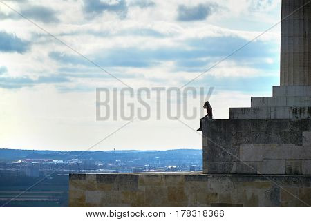 young woman is looking into the landscape on a terrace with dramatic clouds at walhalle in Regensburg. Rear view.
