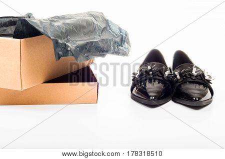 New black feminine beautiful patent leather shoes in a box isolated on white background