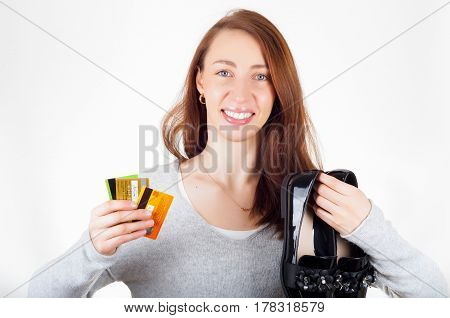 Beautiful woman holding new delivered shoes in one hand and credit cards in other hand. Online shopping concept