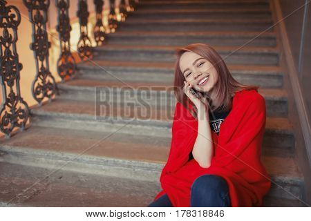 A Young Blonde Girl Talking On The Phone Sitting On The Steps, Wrapped In A Red Blanket. She Is Happ