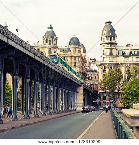 PARIS - SEPTEMBER 20, 2013: Old street metro runs high between buildings. Vintage photo.
