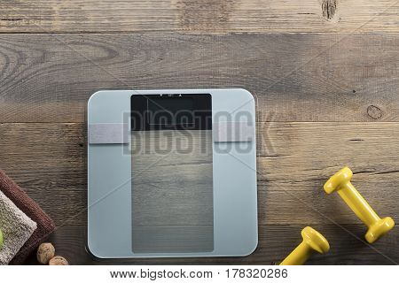 Fitness concept  - weighing machine and dumbells on wooden floor