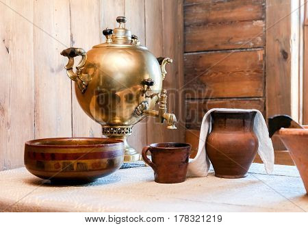 Traditional old copper samovar for tea drinking and ceramic ware on a table in a rural house
