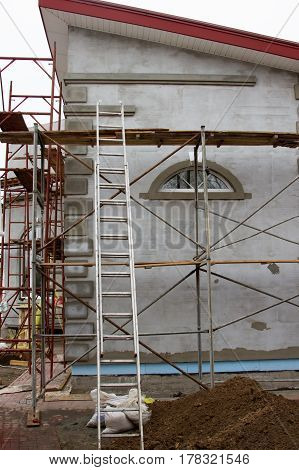 Building a house around which stands scaffolding