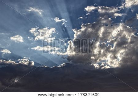 Inspirational: Soft focus storm clouds with strong light rays, suitable for a background layer. Consists of dark storm clouds against a blue sky with light rays peaking through the clouds.