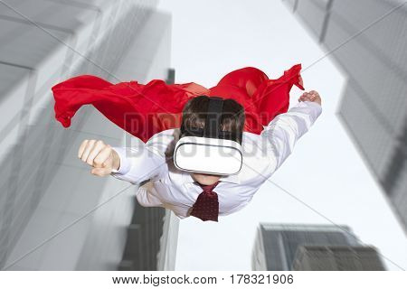Businessman superhero wearing virtual reality glasses flying above a city