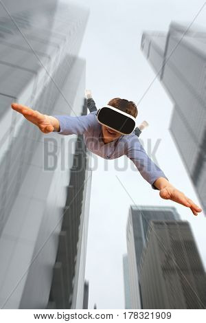 Young man wearing virtual reality glasses flying from a skyscraper