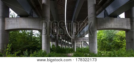 Under the concrete bridge. Ramp of the grade-separated road junction. Industrial construction. Bottom view.
