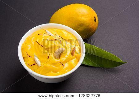 hapus or alphonso Mango pudding / Mango shrikhand or srikhand or amrakhand - Mango dessert with condensed milk magoes and nuts, selective focus over white background