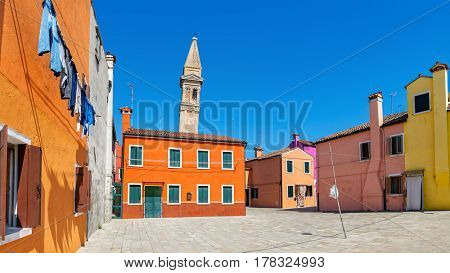 Panoramic view of small courtyard and colorful houses under blue sky on Burano island in Italy.