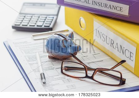 Clean Insurance Form, Folders, Pen, Piggy Bank, Glasses And Calculator
