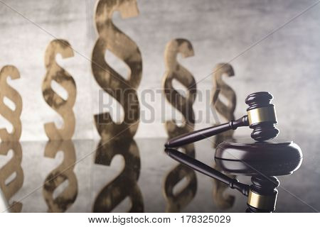 Law and justice theme. Gavel of judge and paragraph symbols on stone background
