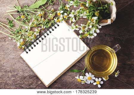 blank notebook with cup of chamomile tea with chamomile flowers on wooden planks on vintage tone