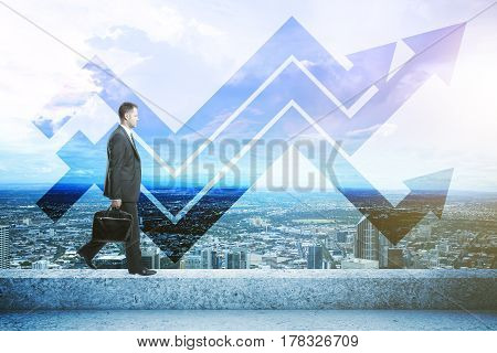 Side view of businessman walking on the edge of concrete rooftop with panoramic city view and upward arrows. Success concept
