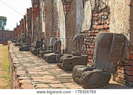 perspective of headless buddha statue in temple ruin wall, bangkok thailand