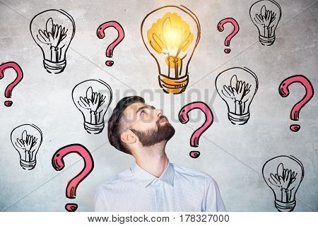 Portrait of curious young man on concrete background with drawn lamps and red question marks. Idea concept