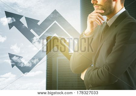 Side portrait of bearded young man with upward arrows on city background with sunlight. Financial growth concept
