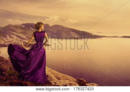 Woman in Elegant Dress on Mountain Coast Fashion Model in Flowing Gown Cloth Looking to Landscape View Outdoor