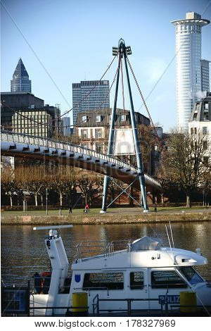 A police boat is parking on the banks of the Main river at the Holbeinsteg-Bridge in Frankfurt.