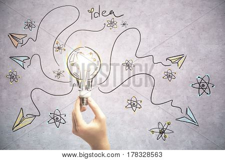 Close up of hand holding lamp on concrete background with arrows and writings. Idea concept