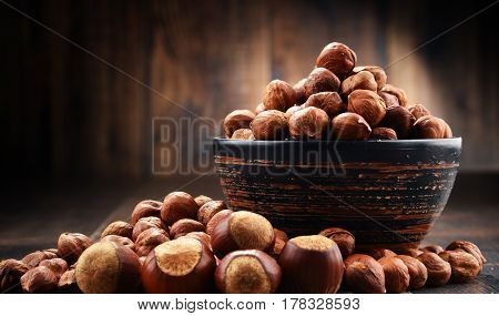 Bowl With Hazelnuts On Wooden Table.