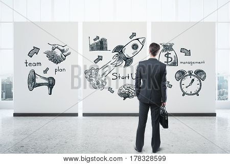 Back view of young businessman with briefcase looking at poster with business icons in interior with city view. Entrepreneurship concept. 3D Rendering