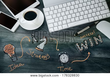 Top view of wooden office desktop with electronic devices coffee cup and creative lamp chess figure and clock sketch. Success concept