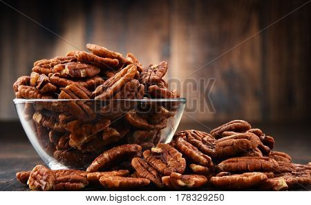 Bowl With Pecan Nuts On Wooden Table.