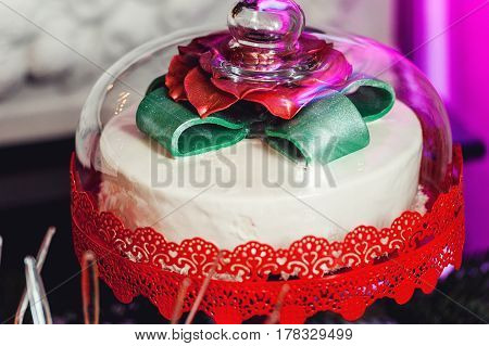 New Year's concept. cake under a glass dome, green bow