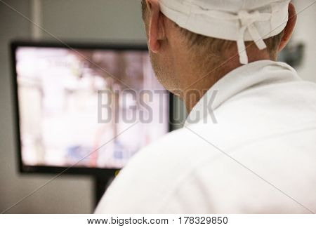 Man (engineer) in a white lab coat and cap looking at the control monitor. Back view.