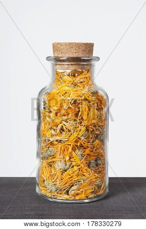 Dried calendula herb inside a glass jar. Herbs and plants for tea.
