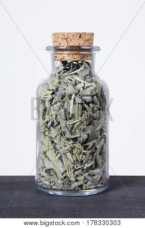 Dried sage herb inside a glass jar. Herbs and plants for tea.