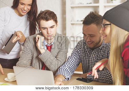 Attractive young men and women at workplace looking at laptop screen together. Team working on project. Teamwork concept
